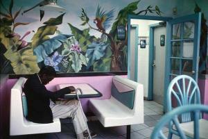 έγχρωμος άνδρας καθισμένος σε λευκό καναπέ κάποιου καφέ στην Αμερική