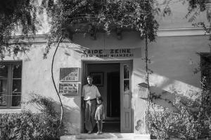 άντρας και μικρό κορίτσι στέκονται στην είσοδο παλιού κτιρίου