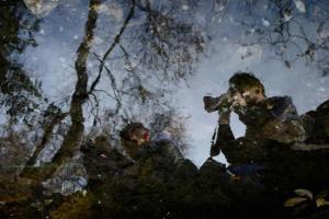 η αντανάκλαση στο νερό δύο φιγούρων φωτογράφων με τις μηχανές τους