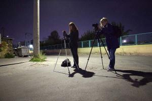 δύο κοπέλες με φωτογραφικές μηχανές στημένες σε τρίποδα φωτογραφίζουν στη νύχτα
