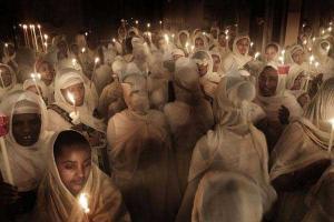 πιστοί σε ιερό ναό με λευκά κεριά και λευκά ρούχα