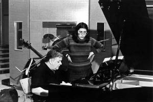 ο μάνος χατζιδάκις παίζει πιάνο και δίπλα του μία κοπέλα τραγουδάει