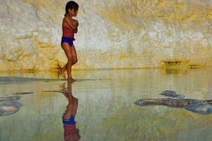 παιδί περπατάει σε κάποια παραλία, από πίσω του ένας βράχος