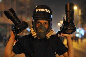 Φωτορεπόρτερ με μάσκα οξυγόνου και δύο φωτογραφικές μηχανές στα χέρια