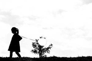 ασπρόμαυρη φωτογραφία / ένα κορίτσι περπατάει με ένα μπαλόνι στο χέρι