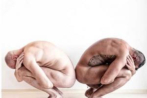 ένας λευκός κι ένας μαυρισμένος άνδρας κάθονται γυμνοί και μαζεμένοι πλάτη με πλάτη