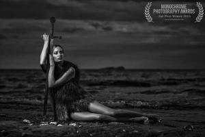 γυναίκα καθισμένη στην παραλία ακουμπά και στηρίζει το σώμα της σε ένα σπαθί
