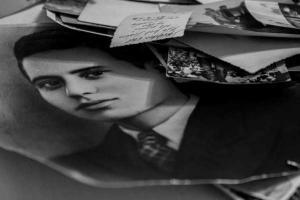 το πρόσωπο ενός άνδρας σε ασπρόμαυρη φωτογραφία και στη μια άκρη ένας σωρός από παλιές φωτογραφίες