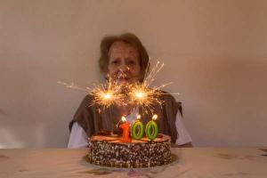 Ηλικιωμένη γυναίκα μπροστά σε τούρτα γενεθλίων σβήνει τα 100 της κεράκια