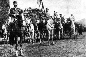 ασπρόμαυρη φωτογραφία με μέλη του ΕΛΑΣ πάνω σε άλογα πριν την είσοδό τους στη Θεσσαλονίκη