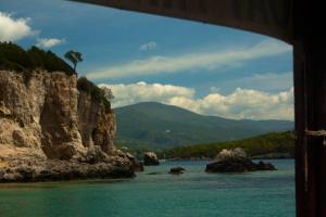 θαλασσινό τοπίο όπου διακρίνονται στο βάθος βουνά της περιοχής και βράχια