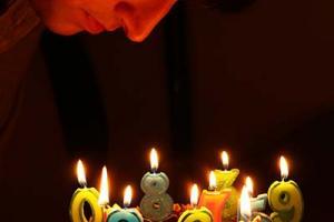 άνδρας σκύβει πάνω από μία τούρτα γενεθλίων με πολλά κεράκια - αριθμούς