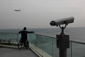 άντρας σε αναπηρικό αμαξίδιο κοιτάζει τη θάλασσα στο βάθος ένα αεροπλάνο και στα δεξιά της φωτογραφίας ένα τηλεσκόπιο