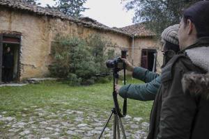δύο κοπέλες φωτογραφίζουν ένα παλιό κτίριο με τη φωτογραφική μήχανη σε τρίποδο