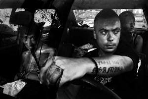 ασπρόμαυρη φωτογραφία τριών ατόμων μέσα σε ένα αυτοκίνητο