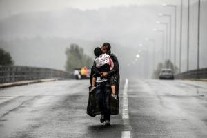 πρόσφυγας στη βροχή κρατάει στην αγκαλιά του το παιδί του