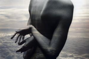 γυμνή κοπέλα με σταυρωμένα χέρια στην πλάτη της και στο φόντο μόνο σύννεφα