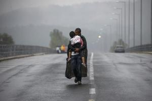 Syrian refugee kisses his daughter as he walks through a rainstorm towards Greece's border with FYROM, near the Greek village of Idomeni
