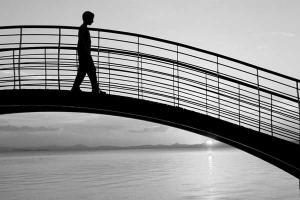 ασπρόμαυρη φωτογραφία με τη σιλουέτα ενός αγορίου πάνω σε μια γέφυρα και στο πισω μέρος θάλασσα