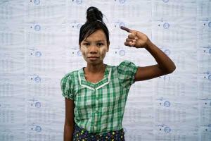 μία αφροαμερικανή με πολύχρωμα ρούχα σηκώνει το μικρό δάχτυλο του χεριού της μπροστά σε ένα τοίχο απο χαρτιά με σφραγίδες