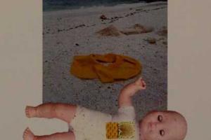 μωρό κούκλα μπροστά σε φωτογραφία παραλίας