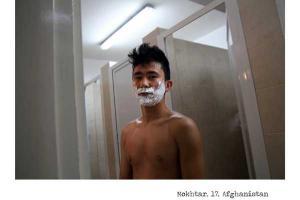 έφηβος από το Αφγανιστάν με αφρό ξυρίσματος στο πρόσωπο στέκεται έξω από τουαλέτα