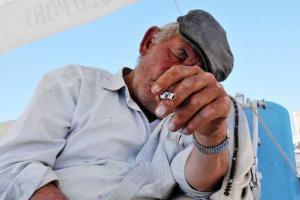ηλικιωμένος άντρας με τσιγάρο στο χέρι κάθεται με γερμένο το κεφάλι στο χέρι του