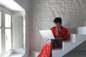 άνδρας με κιμονό κάθεται στα σκαλιά έχοντας στα πόδια του ενα macbook