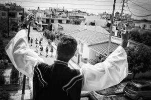 άντρας με παραδοσιακή στολή γυρισμένος πλάτη με τα χέρια ψηλά απευθύνεται σε άλλους παραδοσικά ντυμένους