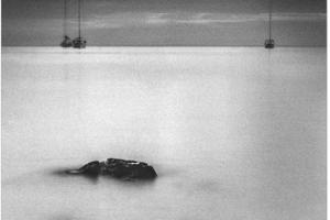 ασπρόμαυρη φωτογραφία παραλίας και στο βάθος δύο καράβια
