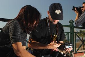 δύο άτομα κοιτάνε μια φωτογραφική μηχανή που κρατά ο ένας στα χέρια του