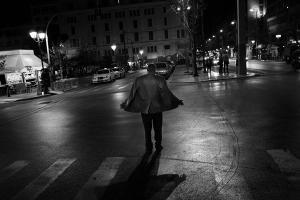 άνδρας περπατάει στο δρόμο με τον αέρα να του παίρνει το σακάκι, ασπρόμαυρη νυχτερινή φωτογραφία