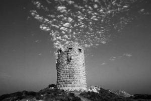 ασπρόμαυρη φωτογραφία ενός πύργου στο Αιγαίο με σύννεφα απο πάνω του