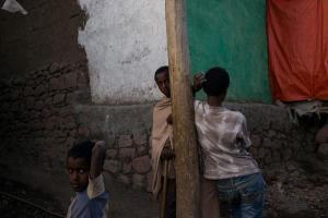 τρία αγόρια από την Αιθιοπία, το ένα γυρισμένο πλάτη σε μια ξύλινη κολώνα
