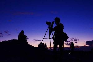 ένας φωτογράφος φωτογραφίζει με μοβ ουρανό