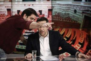 ο Αλέξης Τσίπρας σε τηλεοπτικό στούντιο και δημοσιογράφος του κρύβει το πρόσωπο δείχνοντας του με το χέρι σηκωμένο προς την κάμερα