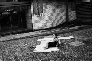 ασπρόμαυρη φωτοραφία, παιδι ξαπλωμένο σε ένα χαρτόκουτο στη μέση μιας αυλής