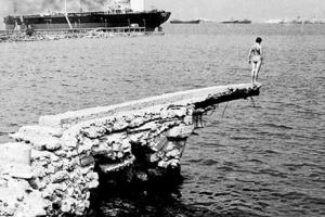 γυμνός κολυμβητής σε βράχο, έτοιμος να πηδήξει στη θάλασσα / στο βάθος πλοίο