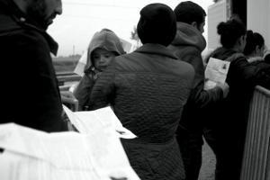 πρόσφυγες κρατάνε στα χέρια τους εγγραφα και ένα παιδάκι