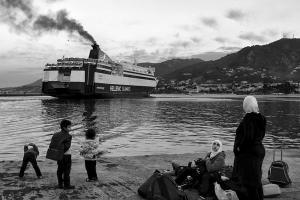 Συριακή οικογένεια κοιτάζει πλοίο που φεύγει από το λιμάνι της Λέσβου, περιμένοντας να επιβιβαστεί σε ένα από τα επόμενα για το λιμάνι του Πειραιά. 2015