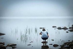 φωτογραφία μίας κοπέλας που στέκεται πάνω σε μία μικρή πέτρα και γονατιστή κοιτά μία λίμνη