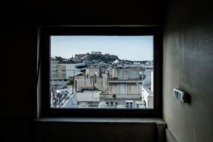 η ακρόπολη όπως φαίνεται μέσα από ένα παράθυρο σπιτιού