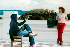 νεαρός καθισμένος σε καρέκλα σε καποια ταράτσα κτηρίου συνομιλεί με μία κοπέλα όρθια