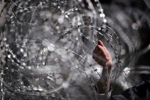 άνθρωπος πιάνει με γυμνό χέρι συρματόπλεγμα συνόρων