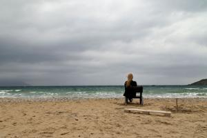 γυναικα κάθεται σε ερημική παραλία, χειμερινό τοπίο