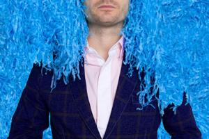 άντρας φοράει μπλε γάντια και άσπρα γυαλιά και έχει καλυμμένο το κεφάλι απο μπλε γκοφρέ χαρτι