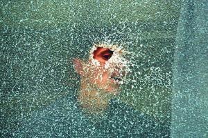 νεαρός βλέπει μέσα απο τρύπα θρυμματισμένου παραθύρου