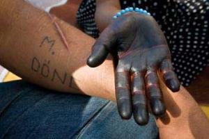 ανοιχτή παλάμη ζωγραφισμένη μαύρη ακουμπά στο χέρι κάποιου άλλου