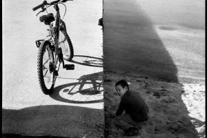 ασπρόμαυρη φωτογραφία ενός παιδιού κι ενός ποδηλάτου