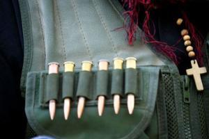 φυσίγγια σε τσέπες στρατιωτικού τζακετ, σταυρός